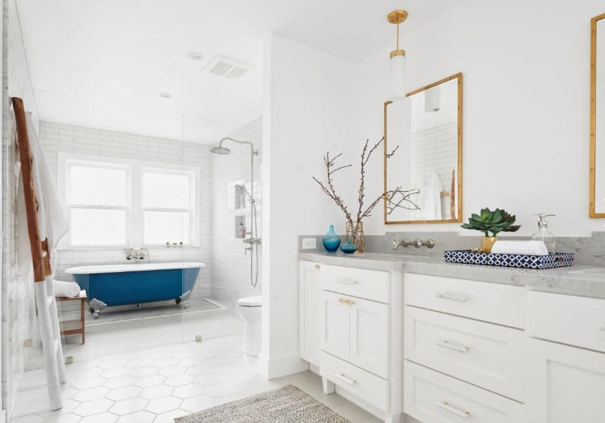 Bright beach style primary bathroom featuring white walls and ceiling. The room has an open shower near the freestanding tub.