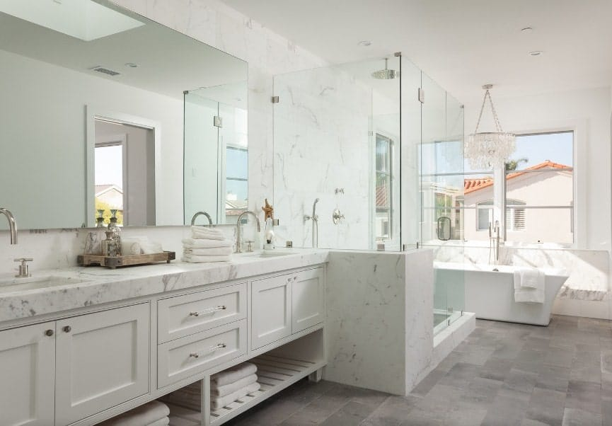 A spacious primary bathroom with a long sink counter with two sinks. The room also has a walk-in shower and a freestanding tub near the windows.