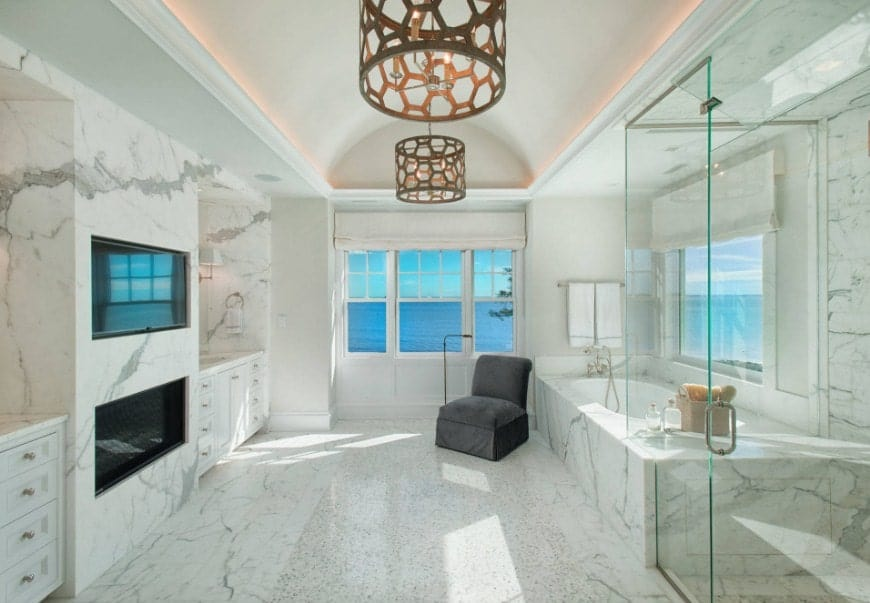 A beautiful beach house covered with marble tiles and has an archway ceiling lighted by fancy ceiling lights. The room offers a fireplace, a TV on the wall, a deep soaking tub and a walk-in shower room.