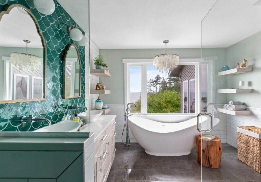 Beach style primary bathroom with elegant green sink counter backsplash along with vessel sinks. The room also has built-in shelves, a freestanding tub lighted by a gorgeous ceiling light and a walk-in shower room.