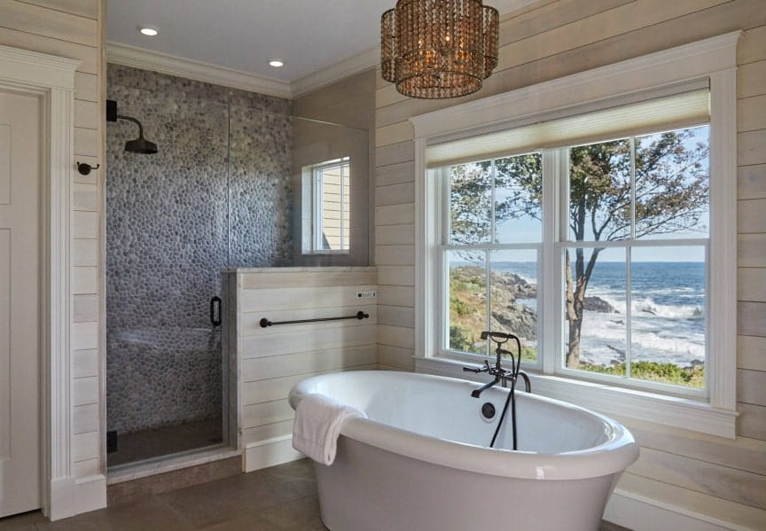 A focused shot at this primary bathroom's freestanding tub lighted by a fancy ceiling light and has a relaxing ocean view through the windows.