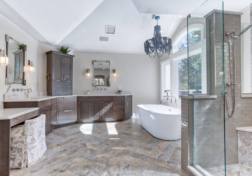 Large primary bathroom with stylish flooring and gray walls. It features a freestanding deep soaking tub and a walk-in shower area.