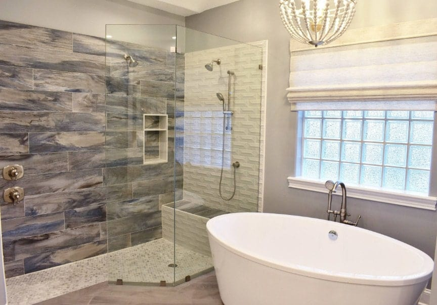 A focused shot at this beach style primary bathroom's stylish walk-in shower room along with a freestanding deep soaking tub lighted by a gorgeous ceiling light.