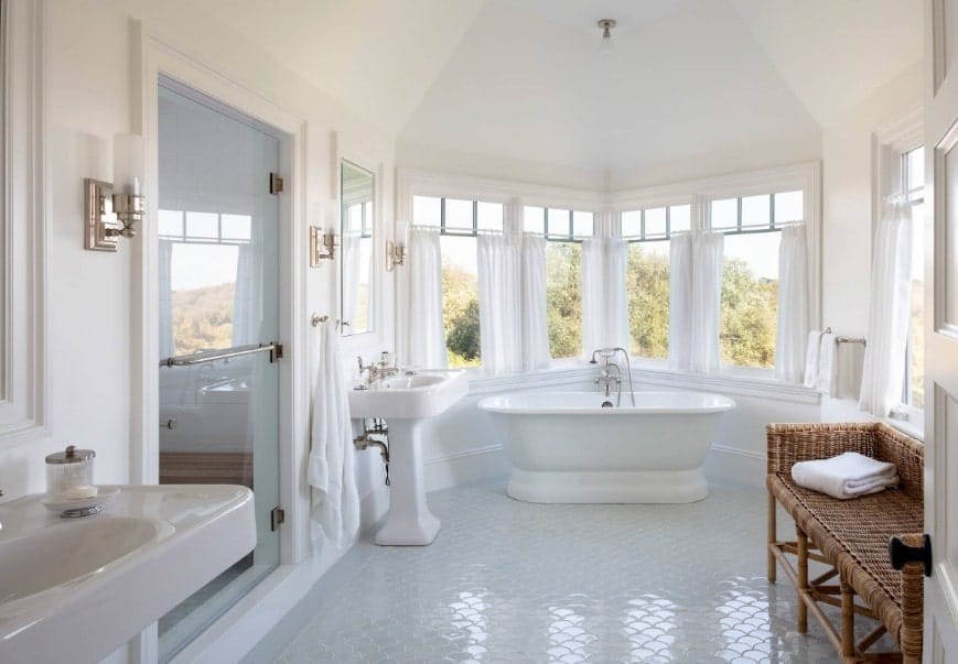 Bright beach house primary bathroom with classy tiles floors and two pedestal sinks. It also offers a freestanding tub near the windows along with a large walk-in shower room.