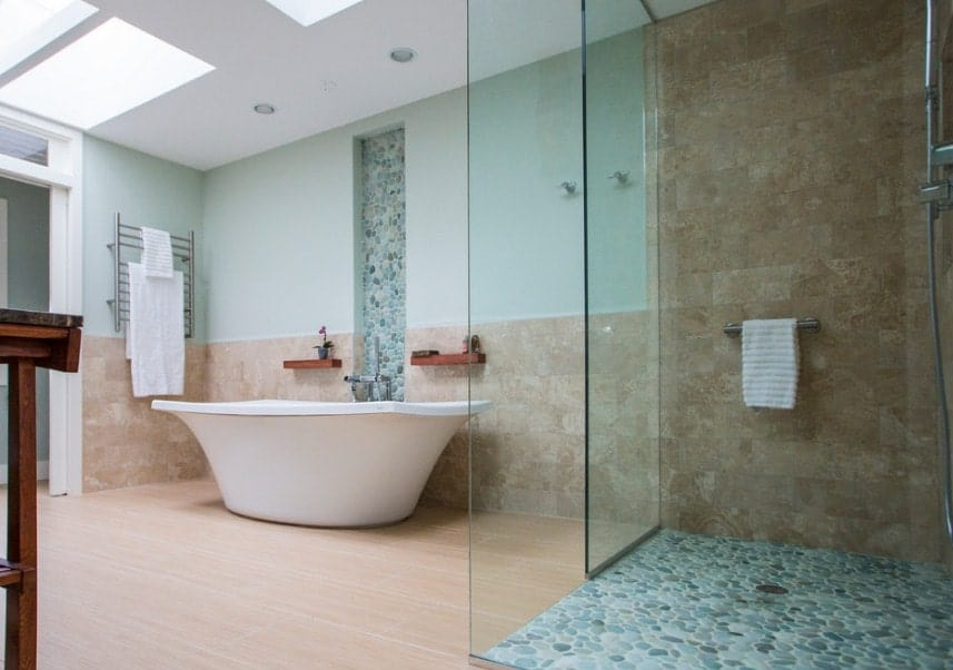 Beach style primary bathroom with skylights on the ceiling. The room offers a freestanding tub along with a walk-in shower area.