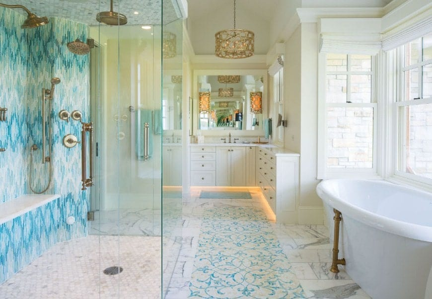A gorgeous beach style master bathroom featuring a beautifully decorated wall of the walk-in shower. There's a freestanding tub on the side as well.