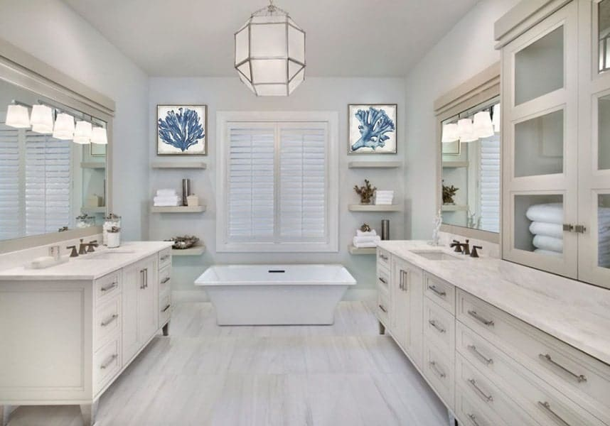 This beach style primary bathroom offers a small freestanding tub along with built-in shelves on each side. There are two sink counters along with a cabinetry.