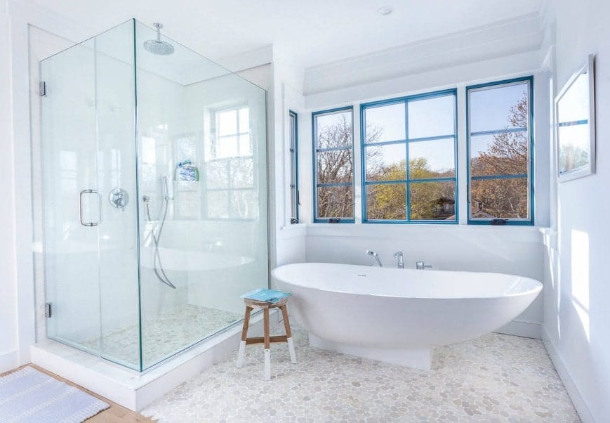 White beach style primary bathroom featuring a boat-shaped freestanding tub along with a corner walk-in shower.