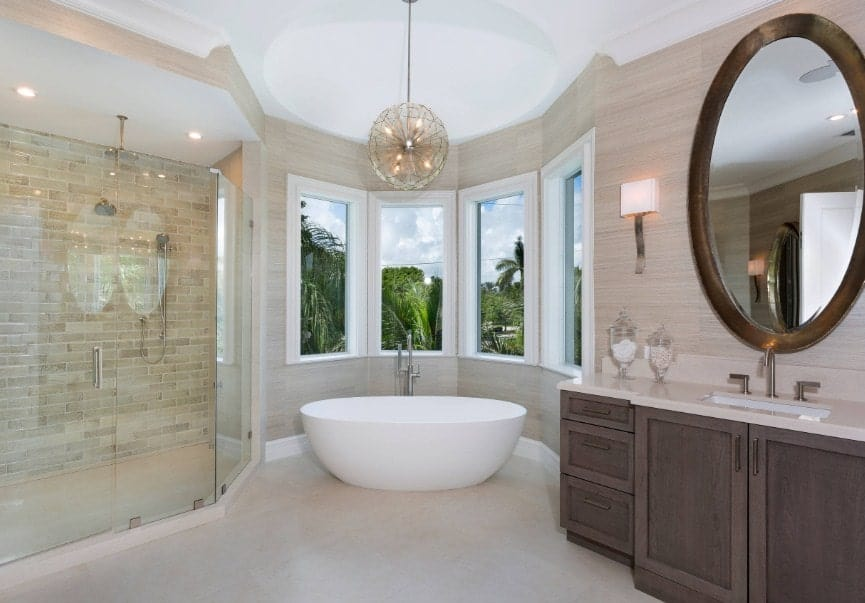 A focused shot at this primary bathroom's freestanding tub in the corner next to the windows and is lighted by a fancy pendant light. There's a walk-in shower head on the side.
