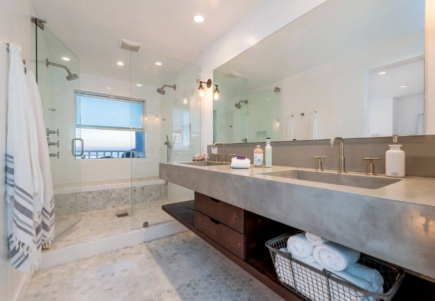 This beach style primary bathroom offers a large shower area with two shower heads along with a long floating vanity with a thick sink counter.