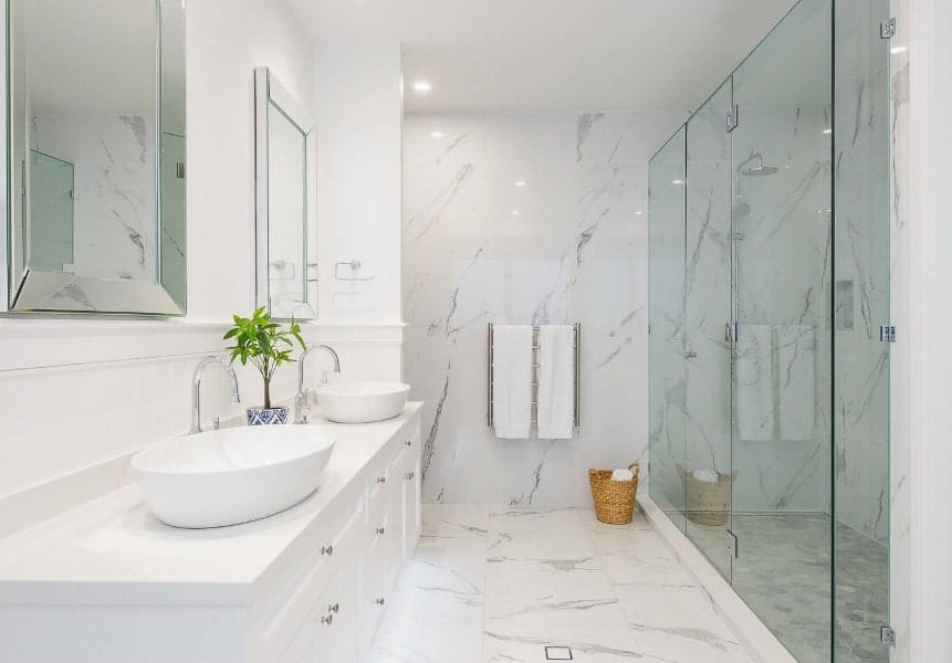 This medium-sized beach style master bathroom offers two vessel sinks and a large walk-in shower surrounded by marble tiles floors and walls.