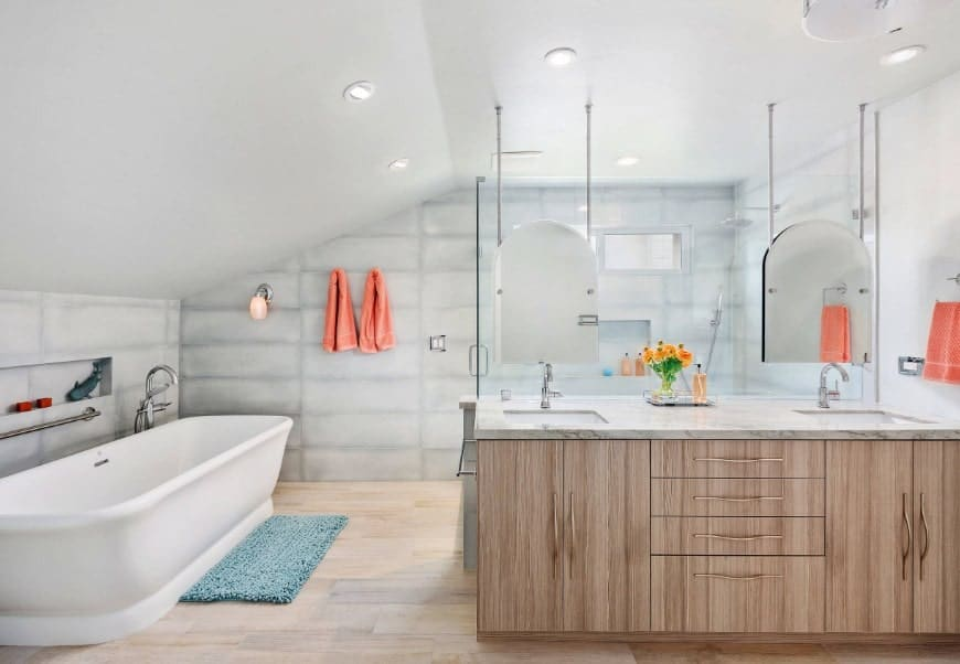 Bright beach style primary bathroom featuring a freestanding deep soaking tub along with a sink counter with two sinks. The walls are very attractive as well.