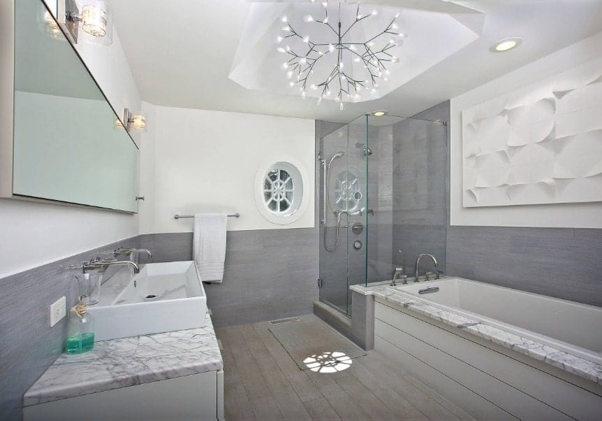 A beach style primary bathroom with a white and gray color scheme. It features a stunning ceiling light along with a corner walk-in shower, a deep soaking tub and a large vessel sink with two faucets.