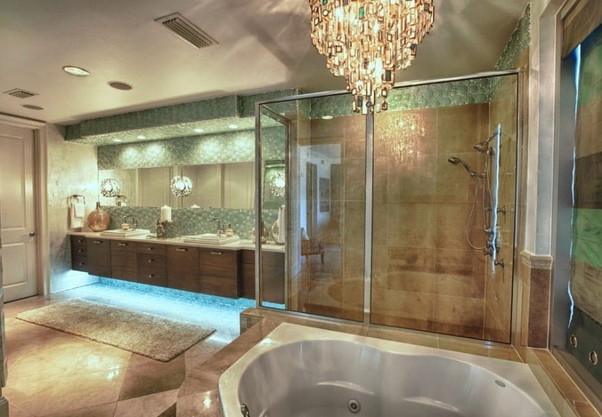An elegant-looking beach style primary bathroom featuring a deep soaking tub lighted by a glamorous chandelier along with a walk-in shower and a floating vanity with a double sink.
