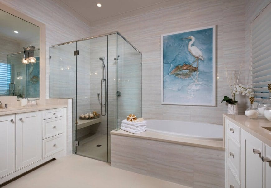 Beach style primary bathroom featuring a deep soaking tub and a corner walk-in shower. There are two sinks lighted by beautiful wall sconces.