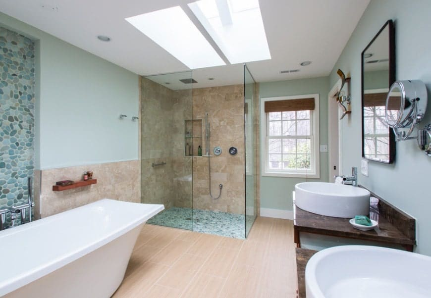 Beach style primary bathroom with green walls and a ceiling with skylights. The room offers a freestanding tub and a walk-in shower, along with two vessel sinks.