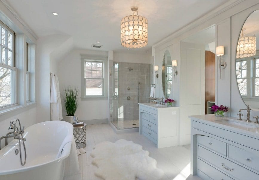 This primary bathroom offers a freestanding tub and a walk-in shower room, along with two sink counters. The room is lighted by a fancy ceiling light.