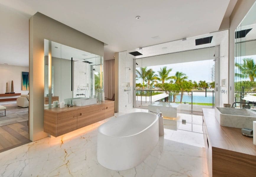 A spacious beach style primary bathroom featuring a freestanding tub along with two vessel sinks on floating vanities.