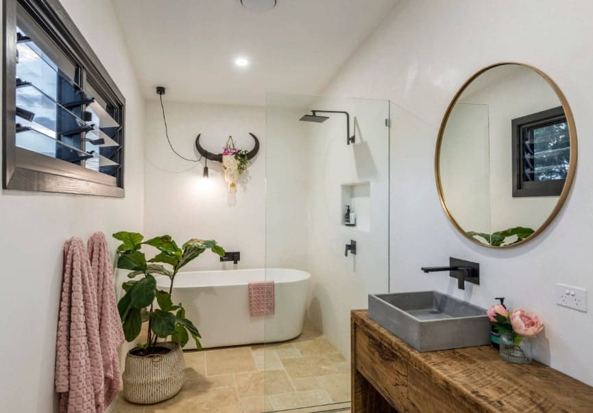 Medium-sized master bathroom featuring a large freestanding tub and a shower area near the tub. There's a vessel sink along with an indoor potted plant.