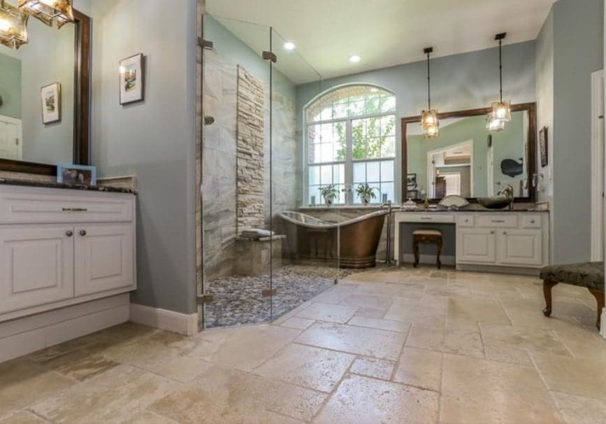 Large primary bathroom with green walls. It features a bronze-finished freestanding tub along with a walk-in shower area.