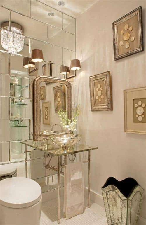 Fabulous bathroom illuminated by traditional sconces and a glam chandelier reflected in the mirrored accent wall that's arranged in bricks.