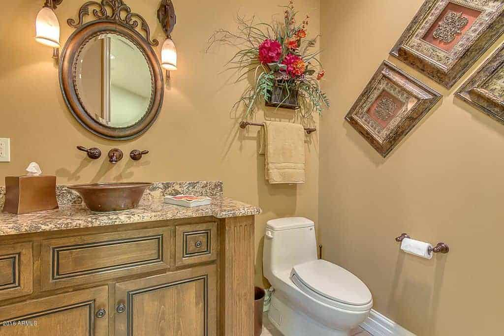 Gorgeous bathroom designed with floral and ornate wall arts along with a round mirror that hung above the wooden vanity topped with a marble counter and bronze vessel sink.