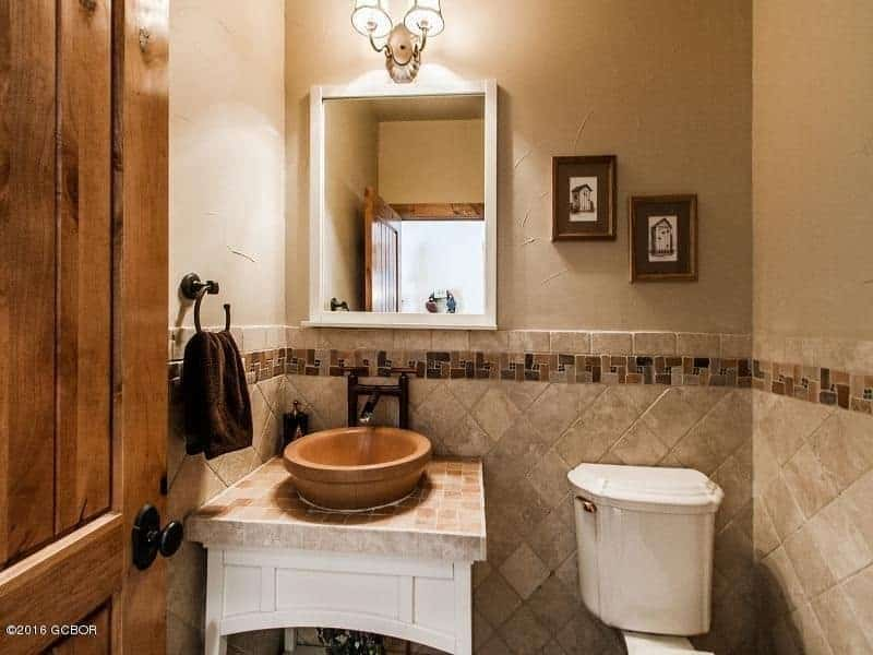 Small bathroom showcases a toilet and washstand with tiled countertop and vessel sink. It includes black framed wall art and medicine cabinet mounted on the beige wall that's clad in ceramic tiles.