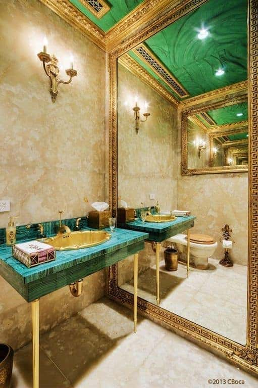 Elegant primary bathroom accented with a green washstand and ceiling lined with ornate gold crown molding. It includes a full height mirror that creates a larger visual space to the area.
