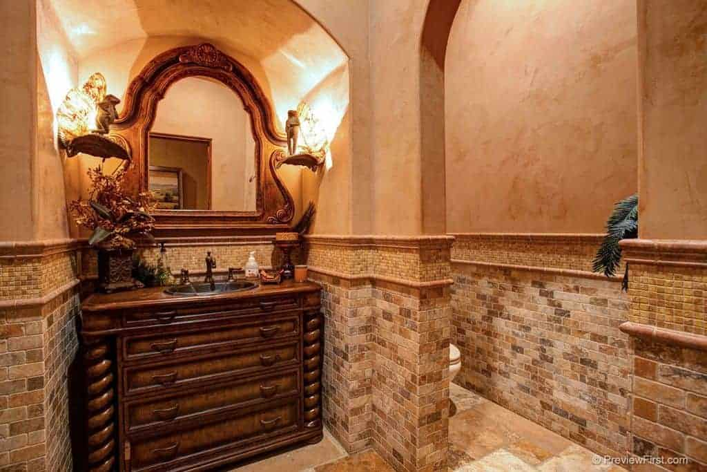 Warm powder room with a carved wood sink vanity paired with a matching mirror that's lighted by stylish sconces. It has limestone flooring and beige walls clad in stone bricks.