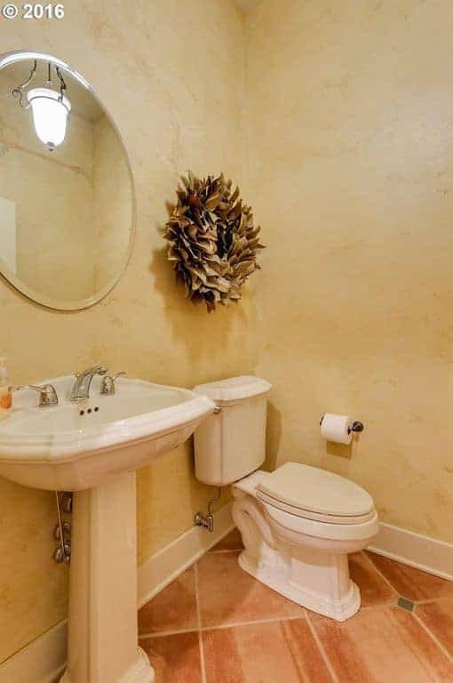 This bathroom is decorated with gorgeous floral wall art and a round mirror that hung above the pedestal sink over tiled flooring.