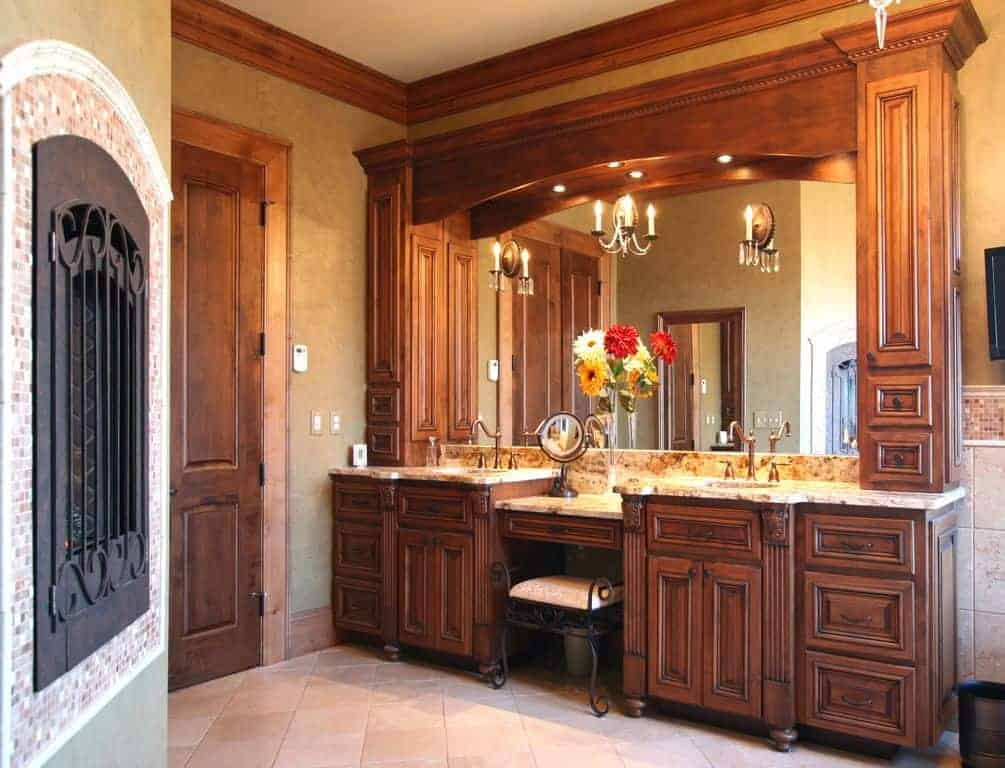A wooden door opens to this beige powder room with an immense dual sink vanity paired with an ornate cushioned stool on limestone flooring.