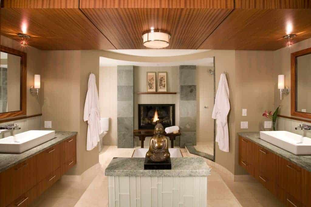 A mini Buddha sculpture brings a classic focal point to this beige bathroom with a fireplace and floating sink vanities that complements with the wood paneled ceiling mounted with flush lights.