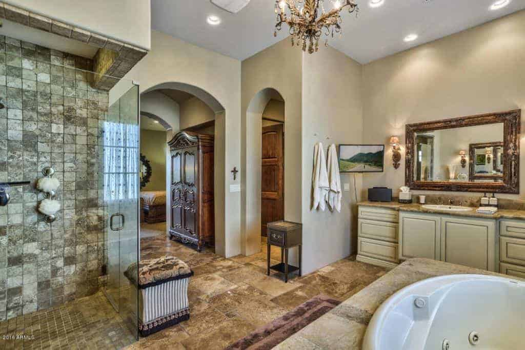 Open archways lead to this beige primary bathroom showcasing a marble top sink vanity and walk-in shower with a cozy stool on its side.