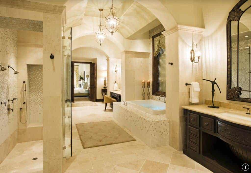 Classy beige primary bathroom with a walk-in shower and deep soaking tub clad in stunning mosaic tiles. The ambient light from the glass sconces and <a class=