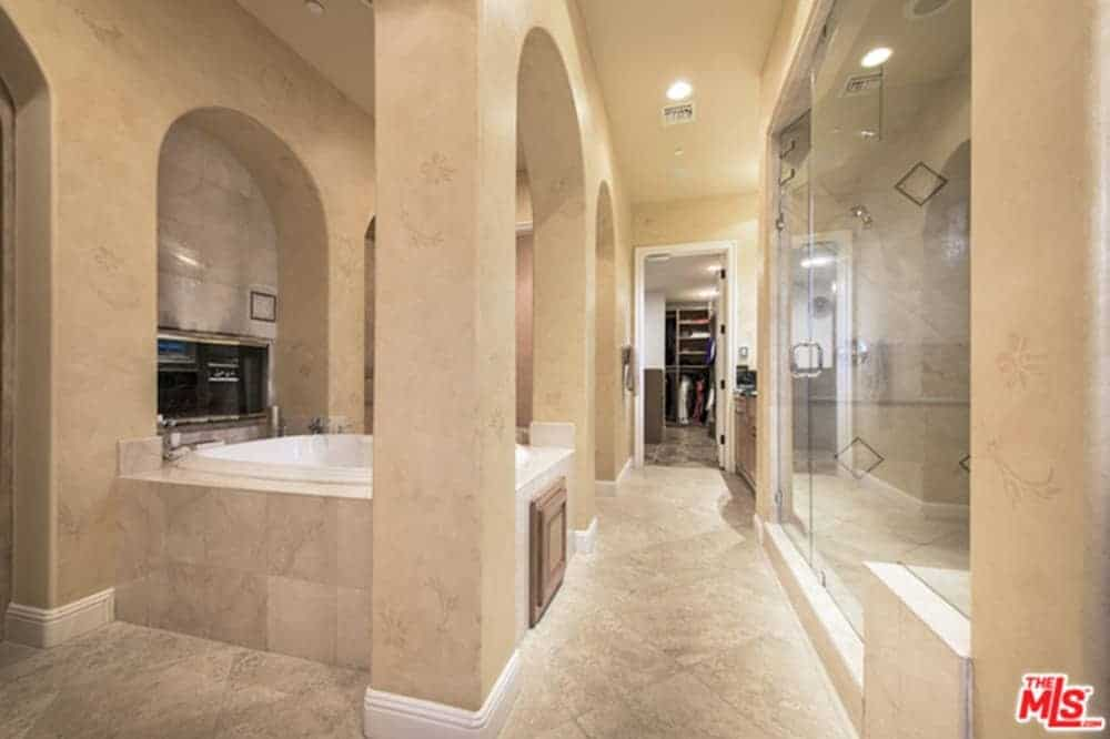 Beige primary bathroom offers a walk-in closet and shower area enclosed in glass. It includes a marble tiled drop-in bathtub framed with open arches.