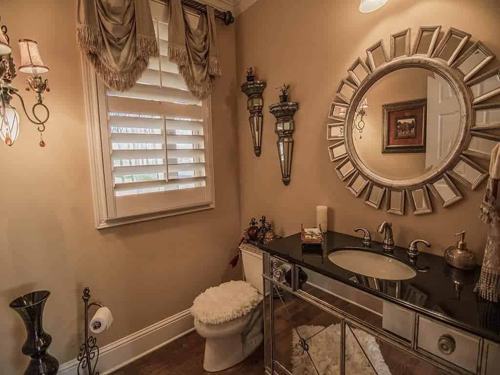 Elegant powder room features a sunburst mirror mounted above the mirrored sink vanity where a white shaggy rug is reflected. It lays on the wood plank flooring and complements with the toilet seat cover.