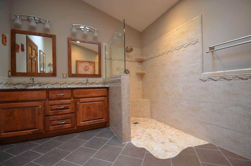 This primary bathroom with vaulted ceiling and brick flooring features a natural wood vanity and walk-in shower that's filled with stainless steel fixtures and tiled seat and shelves.