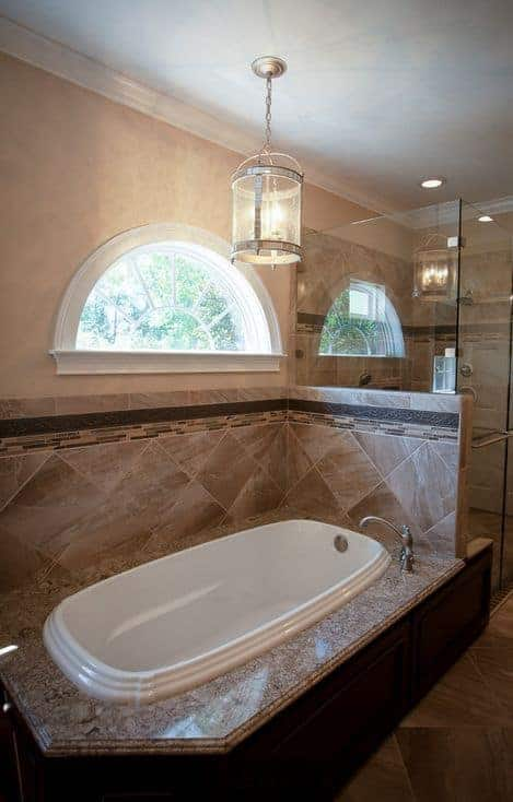 This bathroom features a walk-in shower enclosed in frameless glass and a deep soaking tub underneath a semi-circular window lighted by a glass pendant.