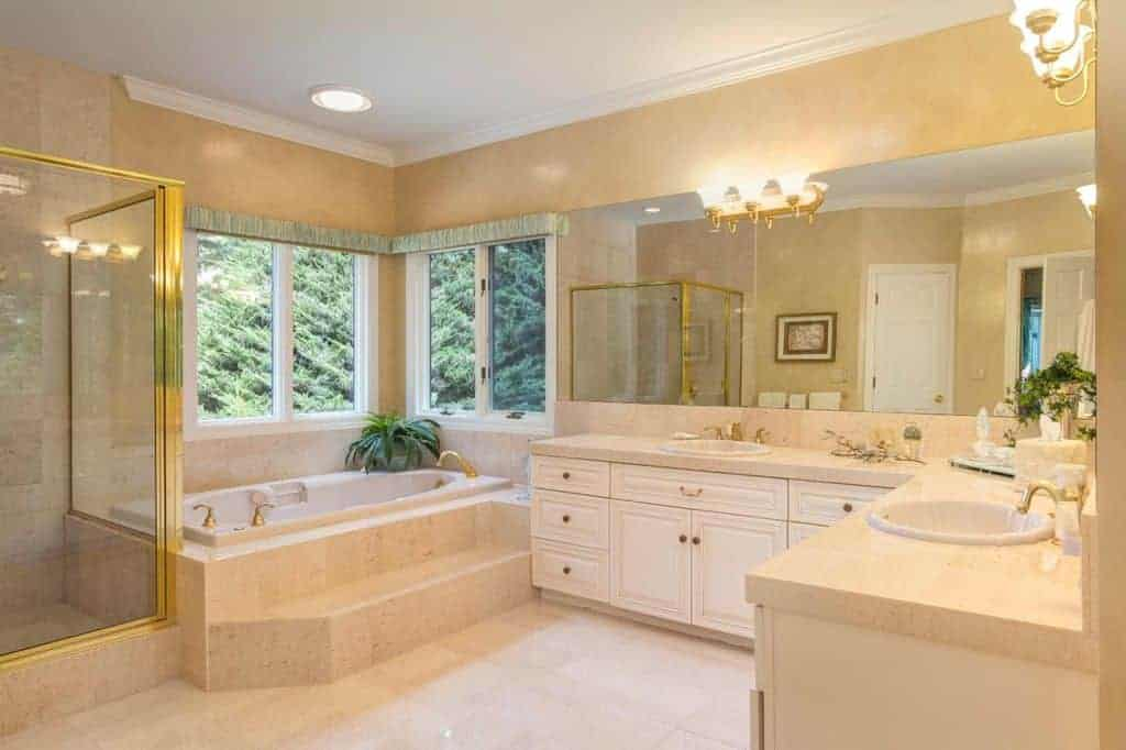 Luxury primary bathroom showcases a drop-in bathtub and walk-in shower with gold linings complementing with the fixtures and sconces mounted on the frameless mirror.
