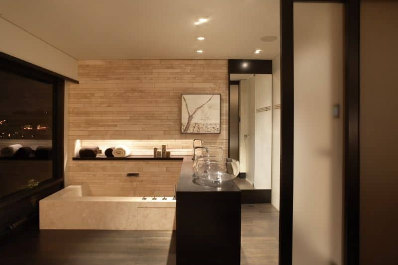 Sophisticated primary bathroom boasts a black vanity topped with crystal glass vessel sinks and a soaking tub attached to the brick wall fitted with an inset shelf.