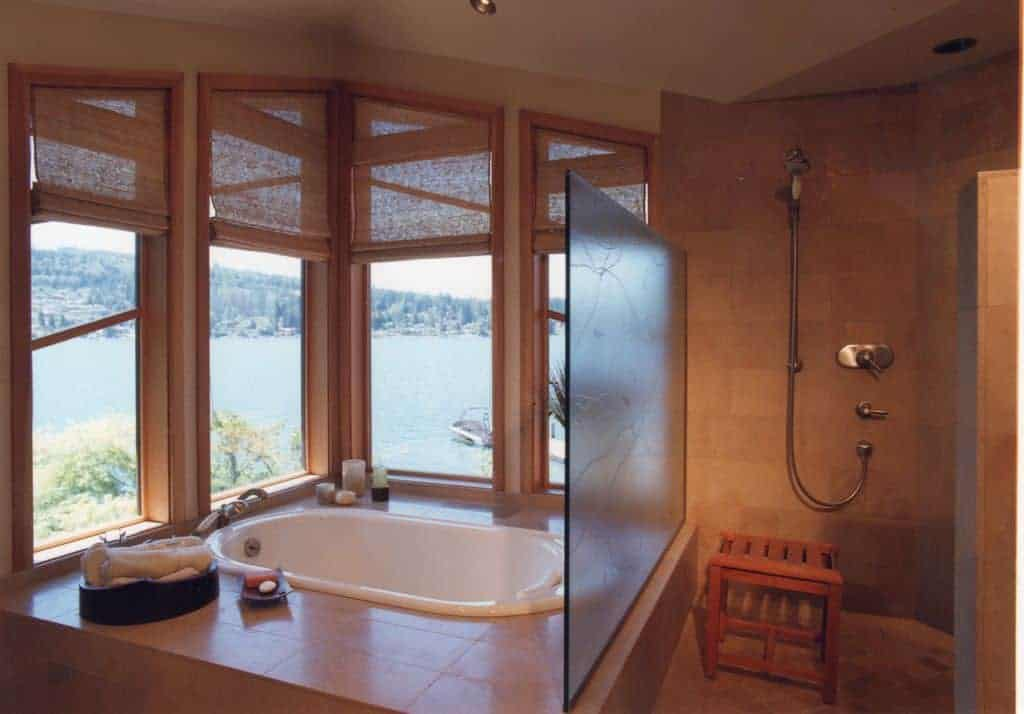 This bathroom showcases a walk-in shower with a wooden stool and a drop-in tub that's perfect for unwinding overlooking an amazing outdoor view through the glass paneled windows covered in wicker roman shades.
