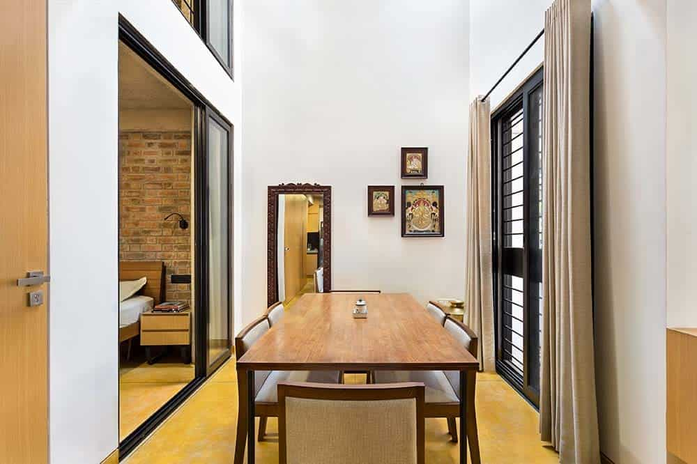 This is a close look at the dining area with a tall ceiling and tall white walls adorned by the wall-mounted artworks and a leaning mirror on the far side of the rectangular wooden dining table and its cushioned chairs on the hardwood flooring.