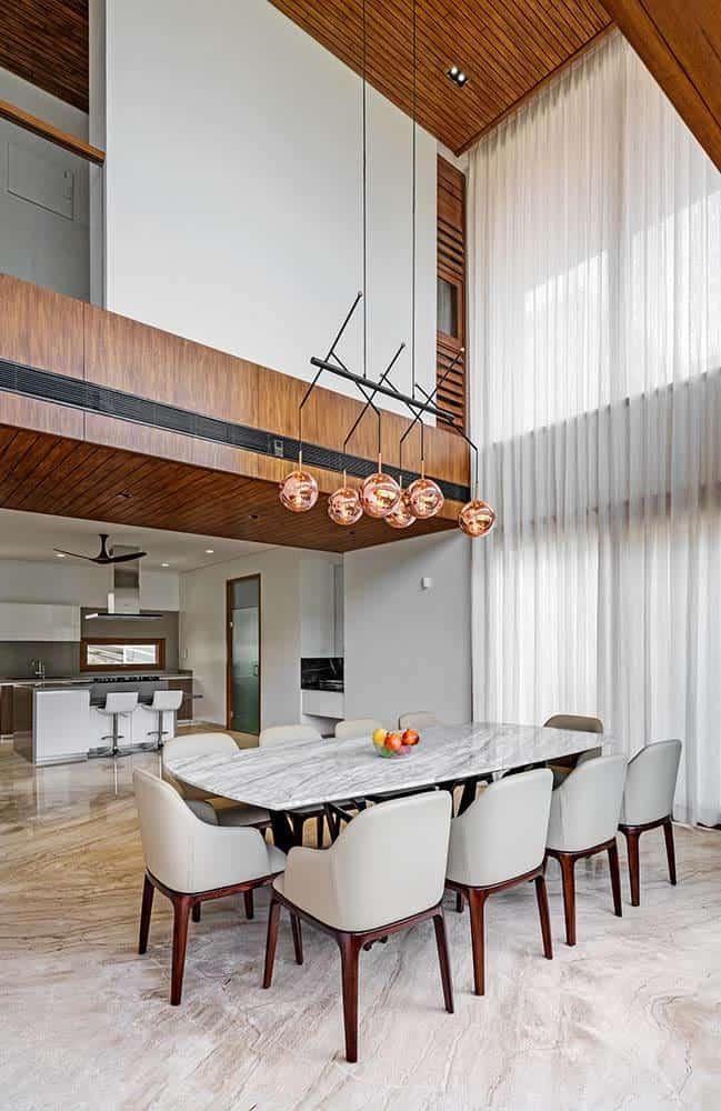 This is the elegant dining area with a tall ceiling that hangs a decorative chandelier over the white marble top of the dining table paired with gray cushioned chairs.