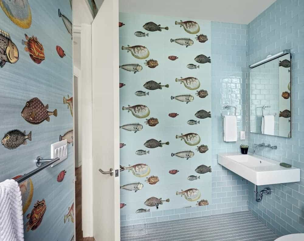 This powder room showcases light blue brick walls accented with gorgeous fishes. It has a wall-mounted sink accompanied by a frameless mirror and stainless steel towel rack.