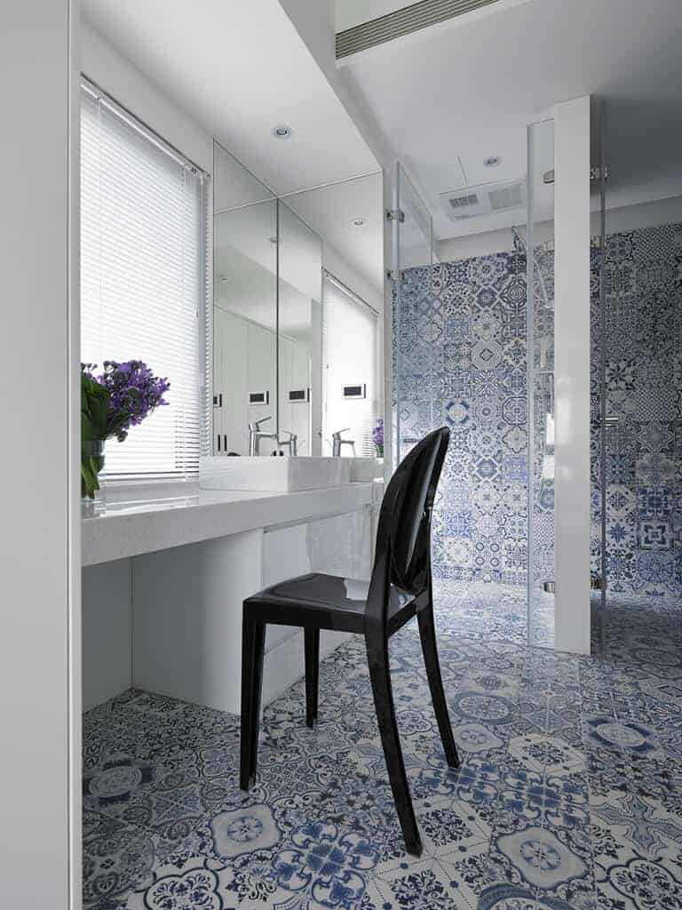 Clad in stunning blue decorative tiles, this powder room offers white vessel sink vanity and a black modern chair facing the glazed window covered in white blinds.