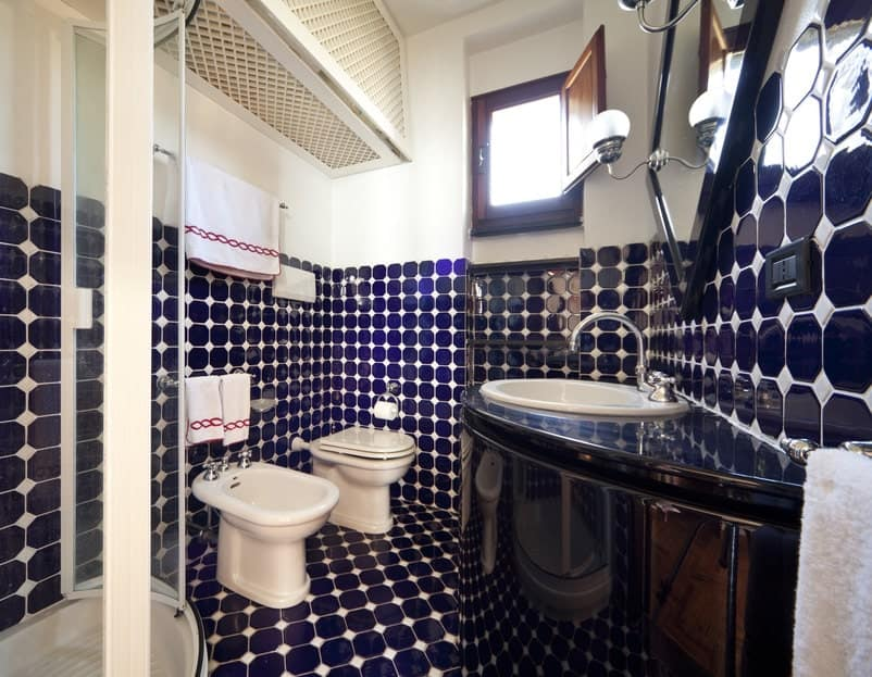 Stunning bathroom offers a walk-in shower and a pair of toilets along with a corner sink vanity in absolute black granite. It is paired with a black framed mirror mounted with glass globe sconces.