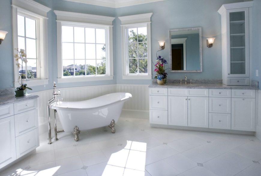 Natural light streams in through the white framed windows in this muted blue bathroom showcasing a clawfoot bathtub that sits in between marble top sink vanities.