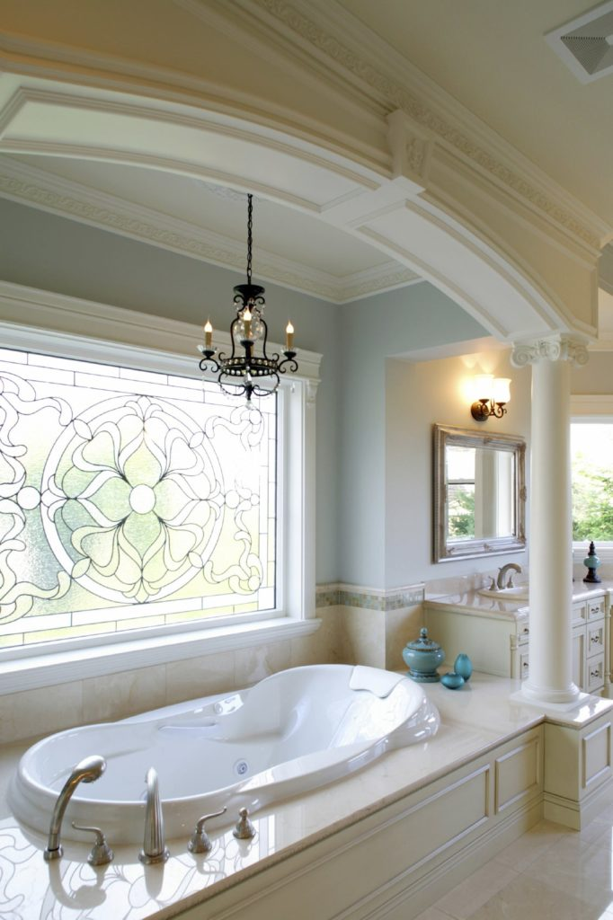 Elegant bathroom with sink vanity and alcove bathtub beneath a charming stained glass window lined with white column. It is illuminated by a wrought iron chandelier and wall sconce mounted above the ornate mirror.