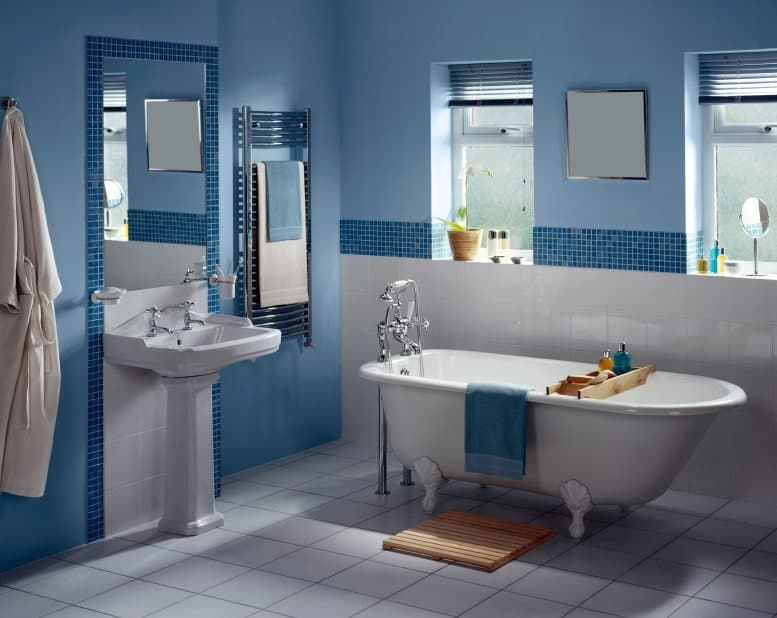 Blue bathroom with a pedestal sink and clawfoot bathtub that sits on white tiled flooring. It has stainless steel fixtures and towel rack mounted next to the mirror.