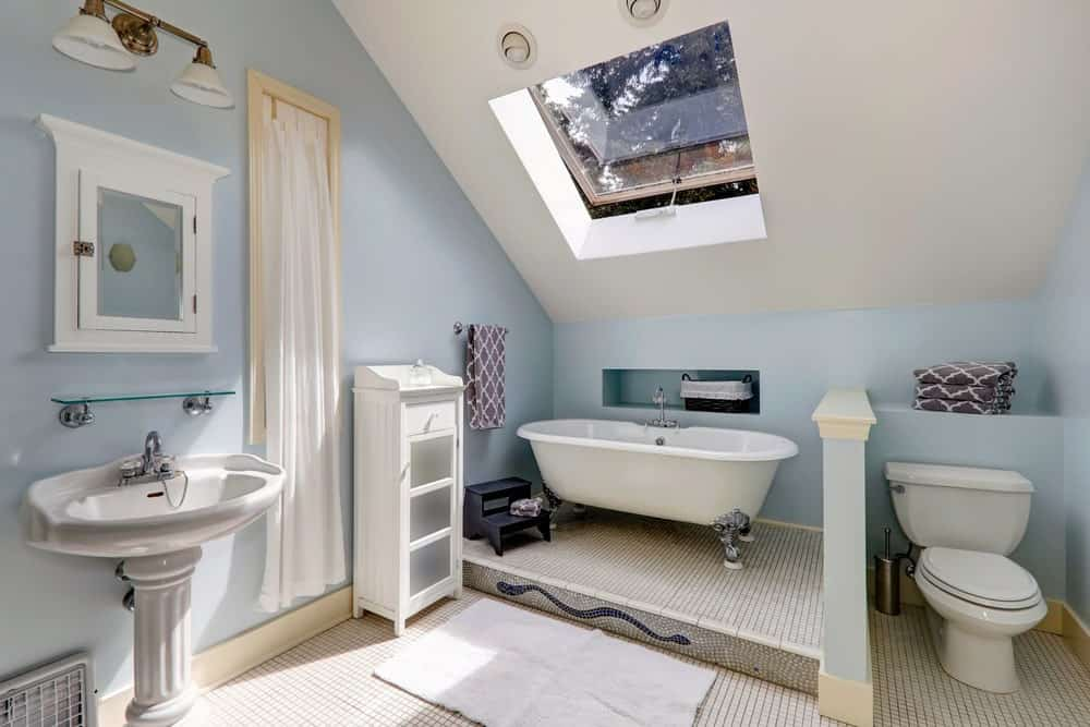 Blue bathroom with white tiled flooring and vaulted ceiling fitted with a skylight window. It is completed with a toilet and tub area along with a pedestal sink paired with a floating glass shelf and white medicine cabinet.